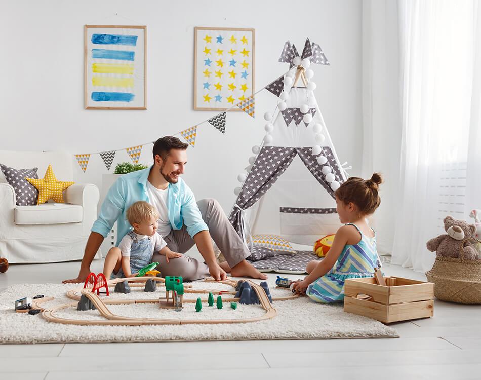 Vater mit Kindern beim Spielen im Kinderzimmer.