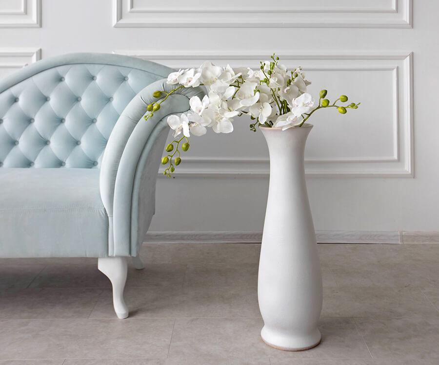 Türkises Barock Sofa und schlanke weiße Vase.