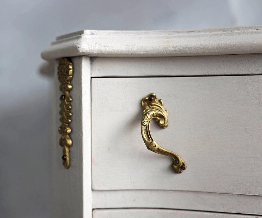 Oberste Schublade einer weißen Barockkommode mit schnörkeligem goldenen Griff.